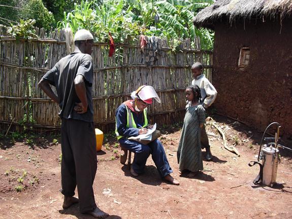 A health extension worker meets with a family whose home will be protected from malaria with IRS. Credit: AIRS.