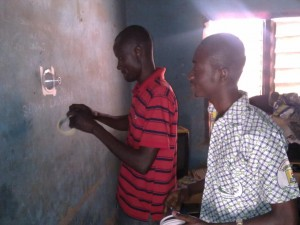 AIRS entomology technicians in Ghana attach WHO cone bioassays to a sprayed wall to test the decay rate of the insecticide Actellic 300 CS. AIRS is now using the new and longer-lasting insecticide in seven PMI-funded countries.